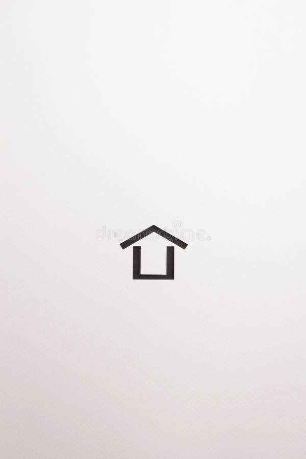 Icona minima di legno marrone scura della casa su fondo bianco immagini stock