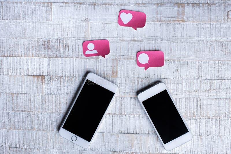 Icone sociali di media del taglio di carta con due Smartphones contenti immagini stock libere da diritti
