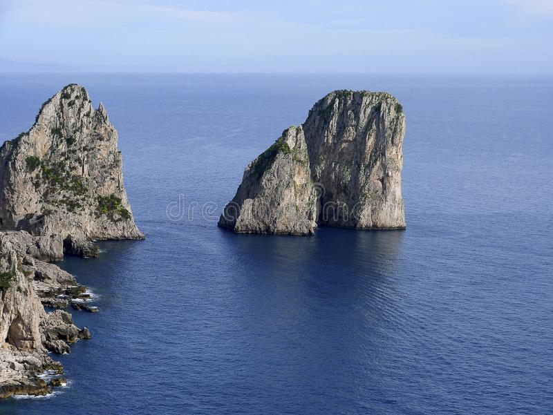 The iconic Faraglioni Rocks off the island of Capri in Italy. Capri is an Italian island off the Sorrentine Peninsula, on the south side of the Bay of Naples. It stock image