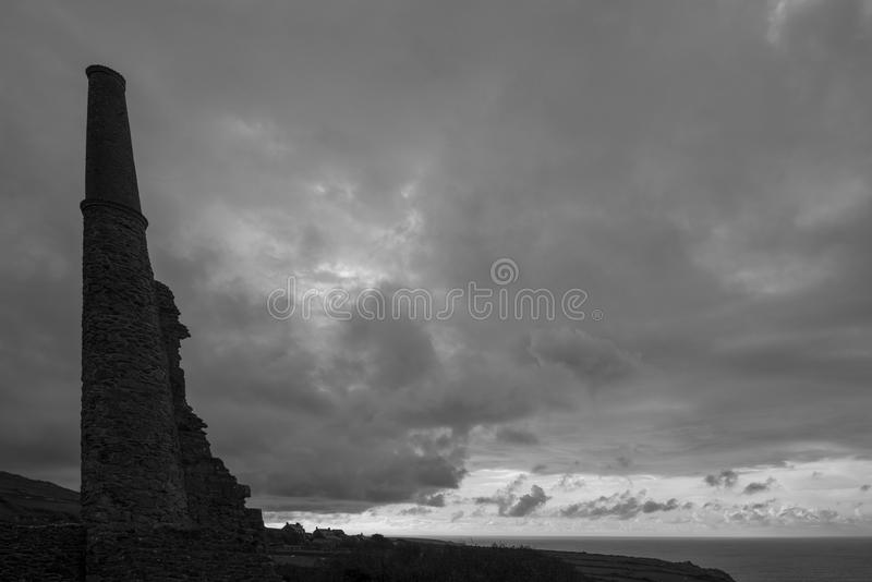 Cornish Tin Mine ruins - in silhouette - Cornwall, England. This iconic image of the ruins of a Tin Mine ventilation shaft and pump engine house reflects the end stock images