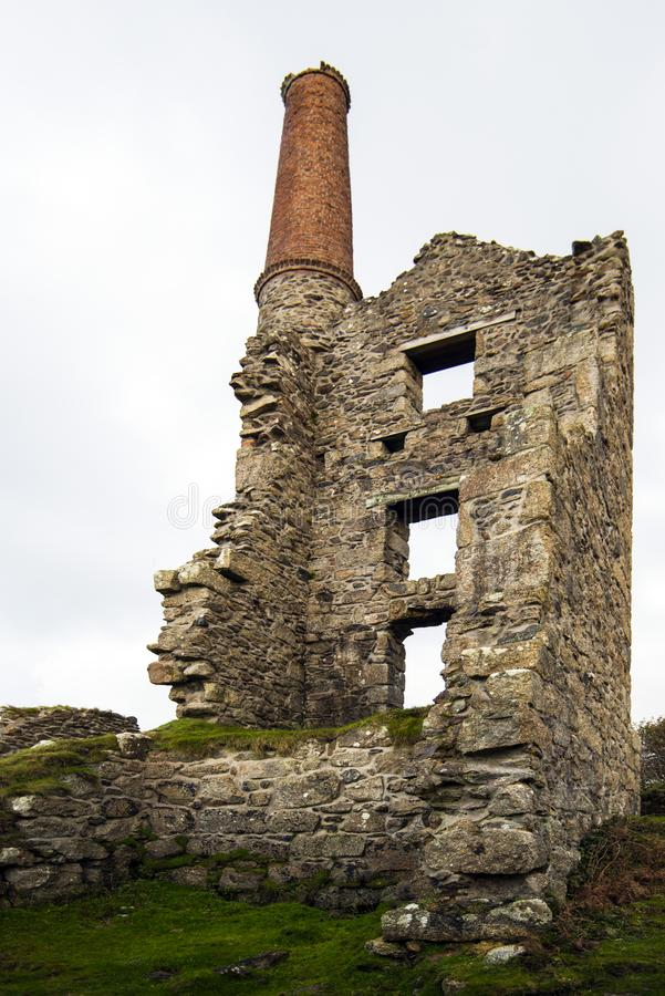 Cornish Tin Mine ruins - Cornwall, England. This iconic image of the ruins of a Tin Mine ventilation shaft and pump engine house reflects the end of the tin royalty free stock photography