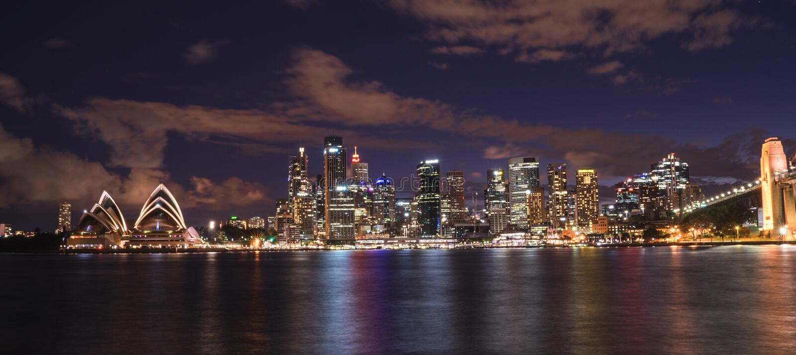 The Iconic Landscape of illuminated Sydney city and Opera House. At night with cloudy sky, view from Kirribilli. The liveable night city. Australia:04/02/18 stock photography