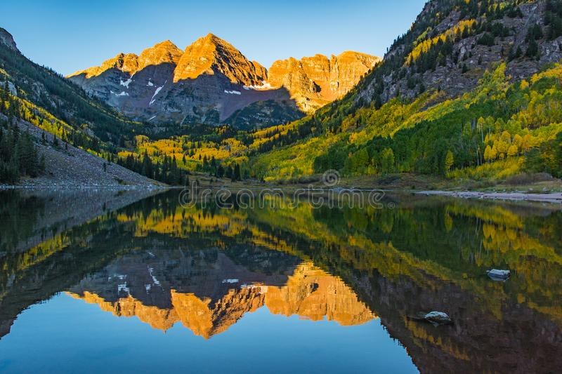 The Iconic Maroon Bells At First Light. Morning`s First Sun Hits the Peaks of the Maroon Bells royalty free stock image