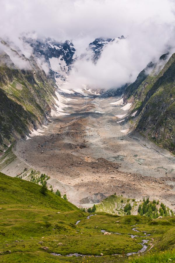 Iconic Mont-Blanc Glacier in Clouds in Green Mountain Landscape.  royalty free stock photo
