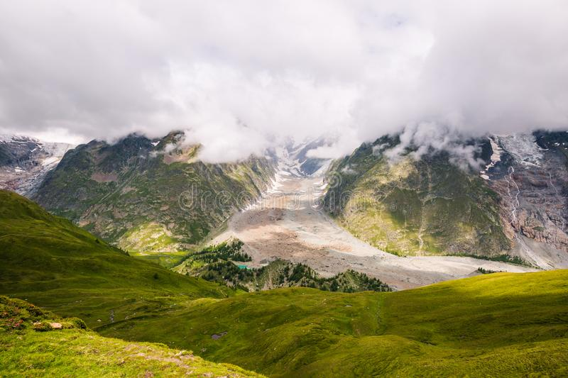 Iconic Mont-Blanc Glacier in Clouds in Green Mountain Landscape.  stock photo