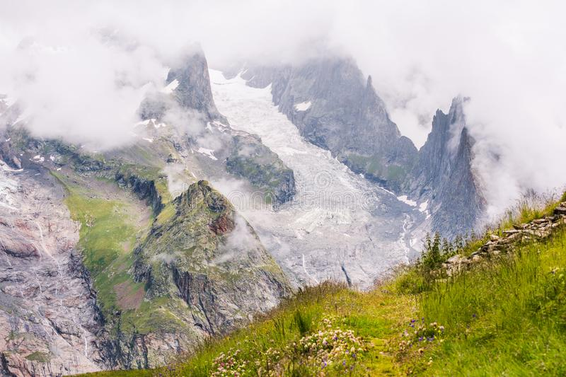 Iconic Mont-Blanc Glacier in Clouds in Green Mountain Landscape.  stock image