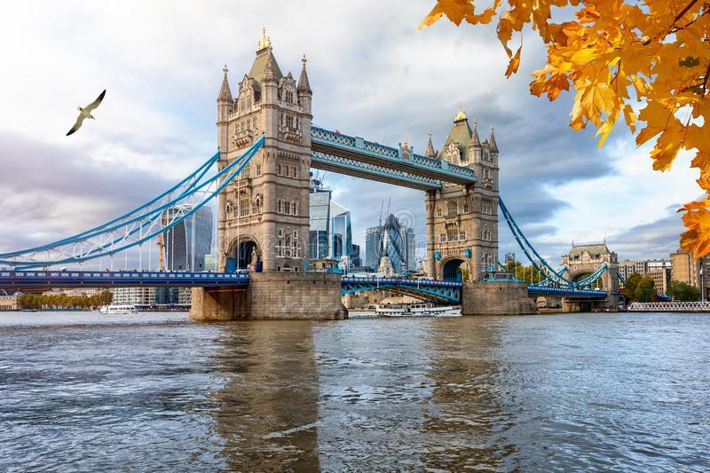 The iconic Tower Bridge on a cloudy afternoon in autumn. London in autumn concept: the iconic Tower Bridge on a cloudy afternoon with reflections in the water stock images