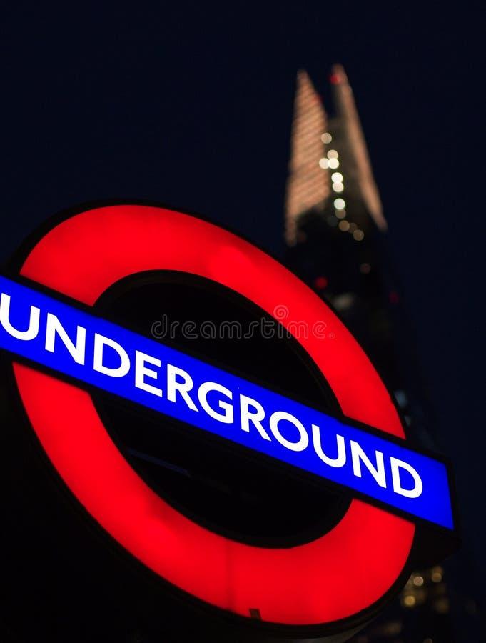 Iconische mening van metroteken en het Scherfgebouw in Londen royalty-vrije stock afbeeldingen