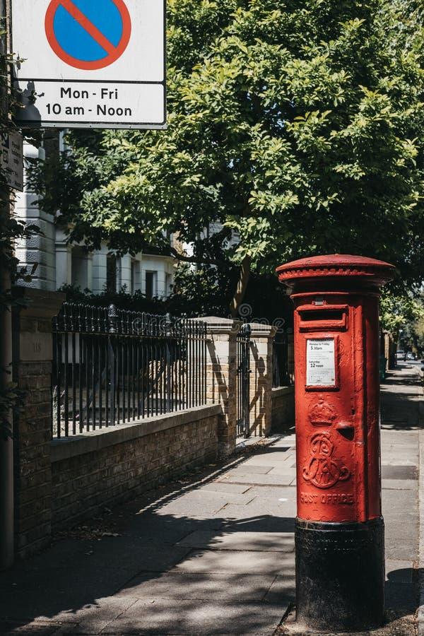 Iconische rode postbox die tot Royal Mail op een straat in Londen behoren stock afbeeldingen