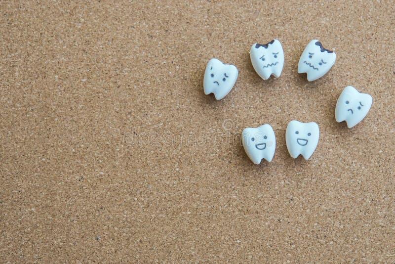 Icono de la historieta de los dientes de la salud e icono decaído en fondo de madera del corcho imágenes de archivo libres de regalías