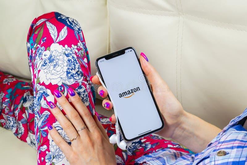 Icono del uso de las compras del Amazonas en la pantalla del iPhone X de Apple en manos de la mujer Icono que hace compras del Am foto de archivo libre de regalías