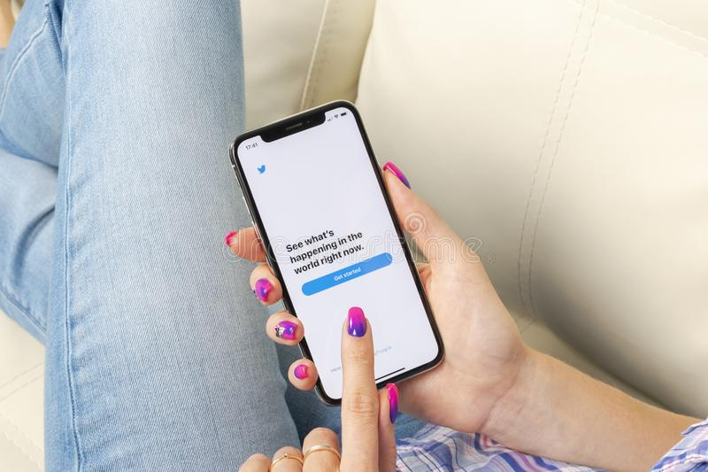 Icono del uso de Twitter en el primer de la pantalla del smartphone del iPhone X de Apple en manos de la mujer Icono de Twitter a fotografía de archivo libre de regalías