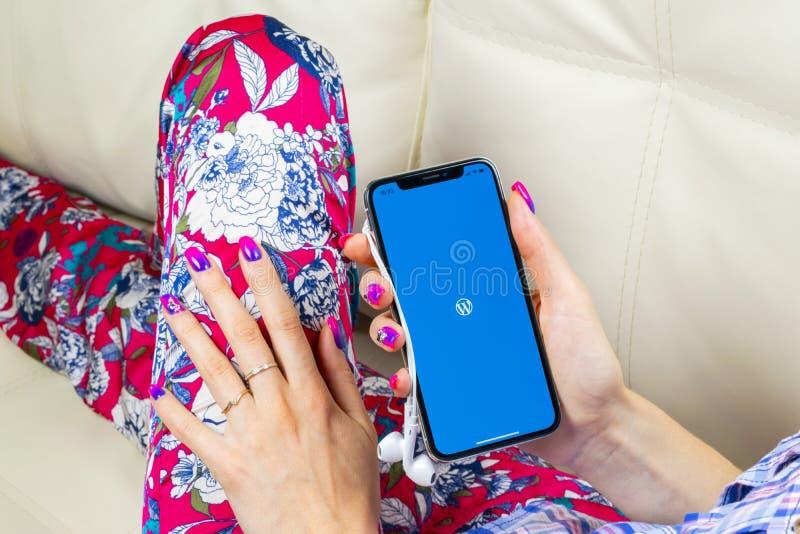 Icono del uso de Wordpress en el primer de la pantalla del iPhone X de Apple en manos de la mujer Icono de Wordpress app wordpres foto de archivo