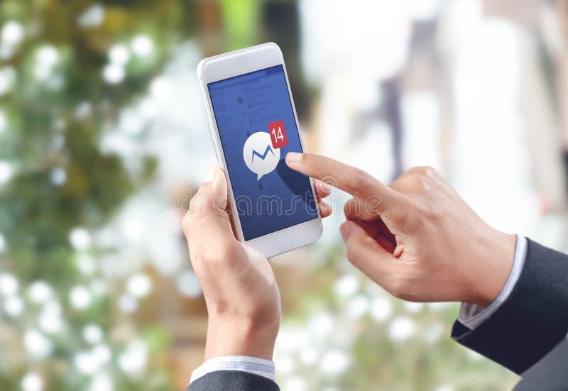 Icono social del tacto de la mano del hombre de negocios medios en la pantalla móvil imagen de archivo libre de regalías