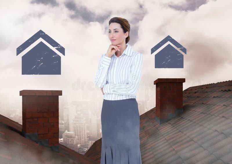 Iconos caseros y empresaria que se colocan en los tejados con la chimenea y la ciudad nublada imagen de archivo