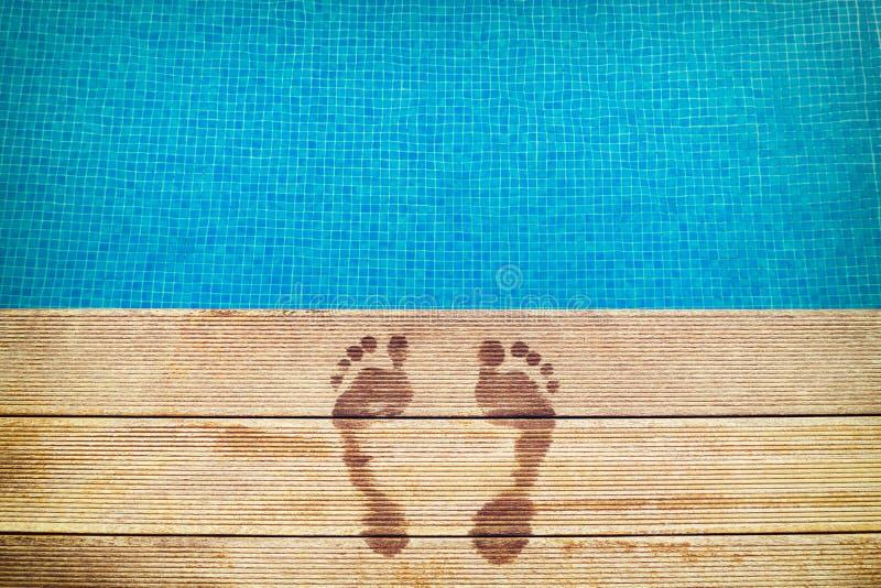 : icture av fotspår på träyttersidan med den blåa simbassängen på bakgrunden royaltyfria bilder