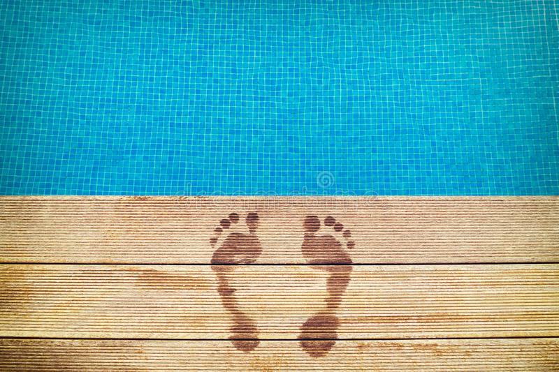 :icture of footprints on the wooden surface with blue swimming pool on the background royalty free stock images