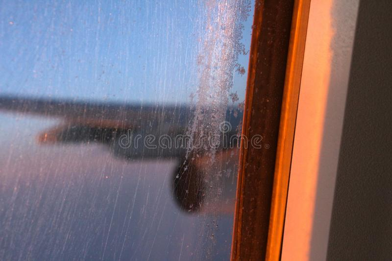 Icy airplane window in flight royalty free stock photography