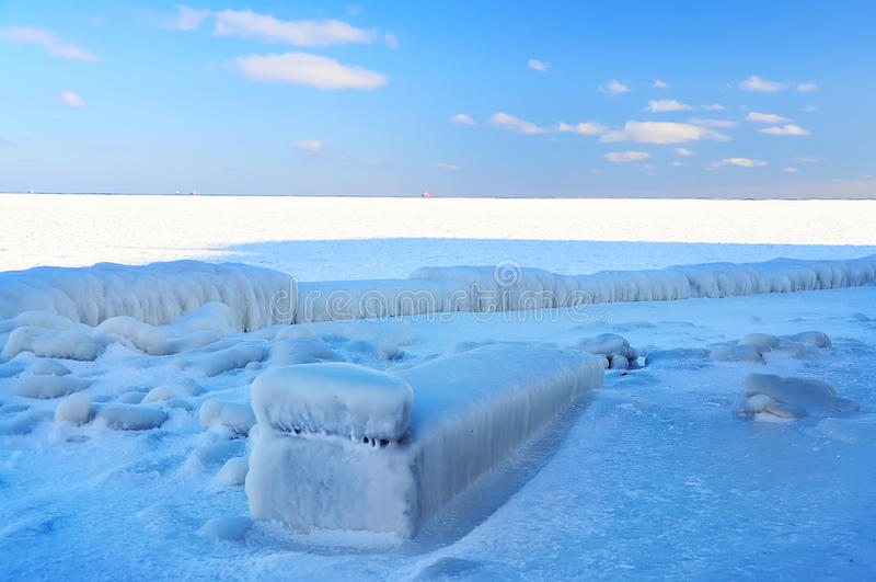 Icy beach. Chaise longue covered with ice. Frozen sea to the horizon stock photography