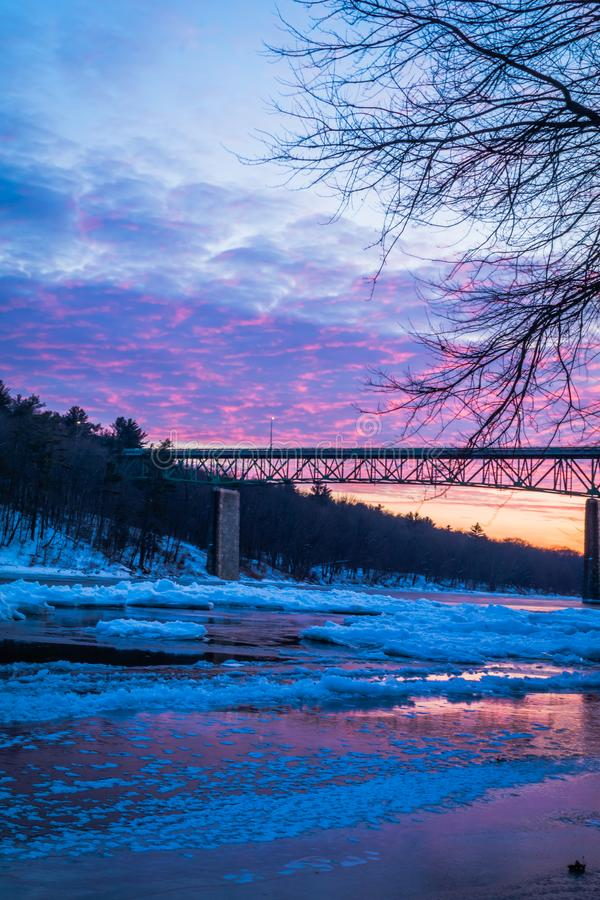 Icy Delaware River reflects the vivid sunset near Milford Bridge, PA, portrait. Icy Delaware River at vivid sunset near Milford Bridge, PA. Winter scene, icy stock photo