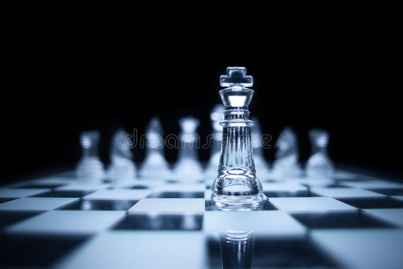The icy knight in darkness. Photo of chess king standing in front of the same colour set in black background royalty free stock photo