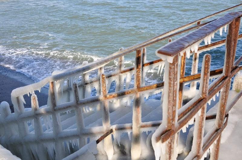 Icy staircase. Descent to the sea. Frozen steps. Frosty winter day on the coast. Close-up stock images