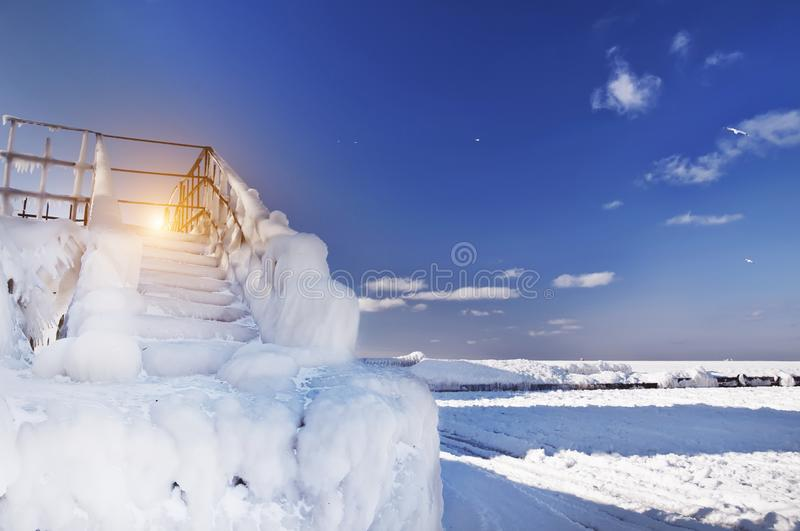 An icy staircase on the shore of a frozen sea. Bright sunny winter morning. stock image