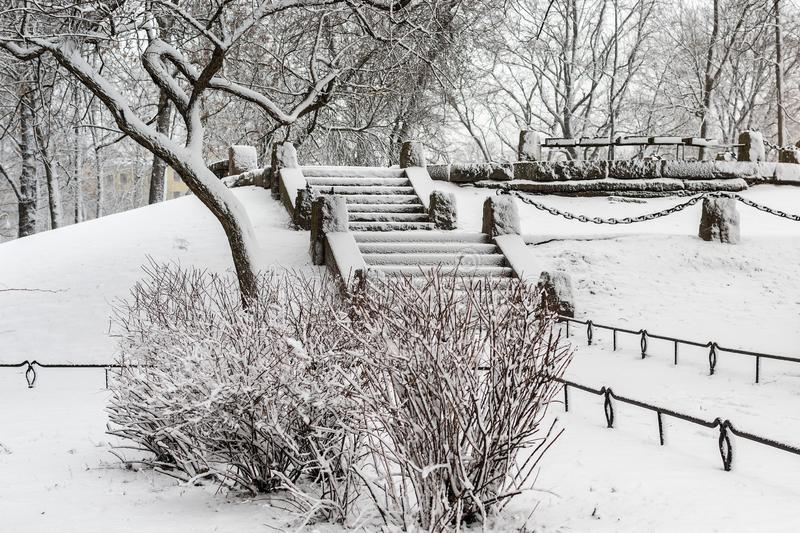 Icy stairs in the winter Park. An icy staircase in a winter Park with bushes and trees covered in snow royalty free stock photos