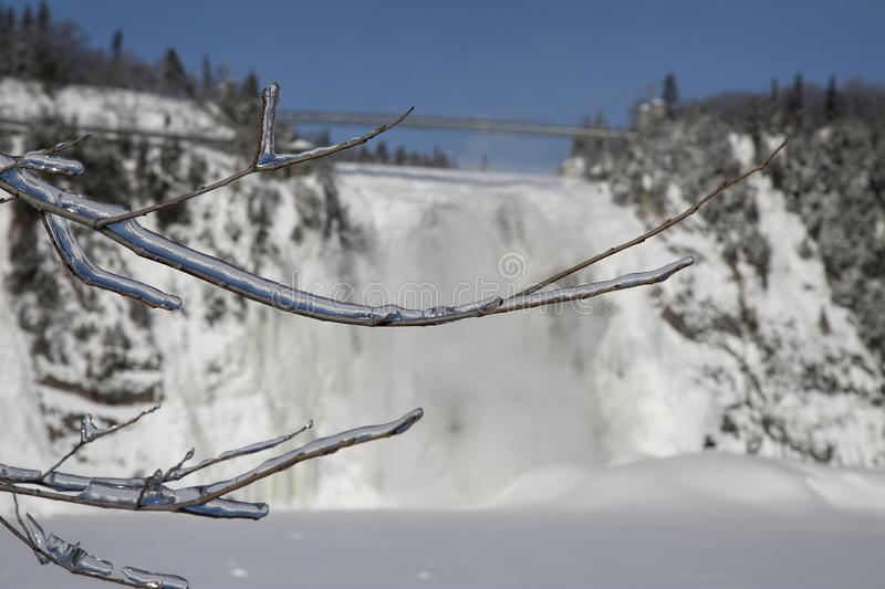 Icy Tree Branches Silhouetted Against Montmorency Falls. Located 15 minutes from Old Quebec, the Montmorency Falls Park is a spectacular historic site. The falls royalty free stock photo