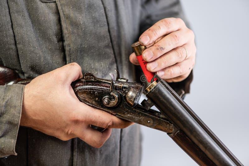 Idé - dödande till och med avundsjuka eller hämnd Man att utrusta upp den dubbelpipiga hagelgeväret av kassetter, processslut, re royaltyfria foton