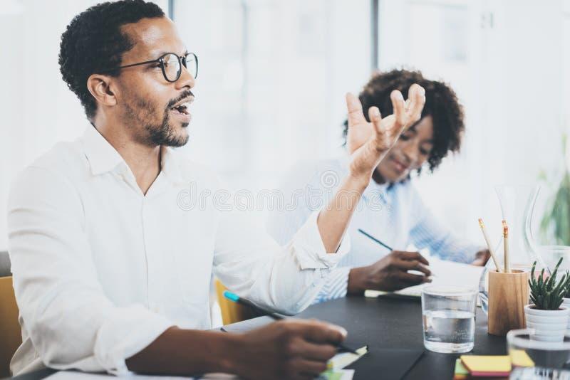 Idé för affär för man för svart afrikan explaning i mötesrum Två unga coworking personer som tillsammans arbetar i ett modernt ko fotografering för bildbyråer