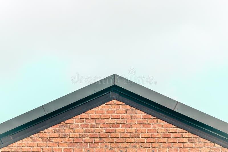 Idé för begrepp för stil för land för hus för röd tegelsten för gaveltak mot klart hem för himmelbakgrundssaknad royaltyfri foto