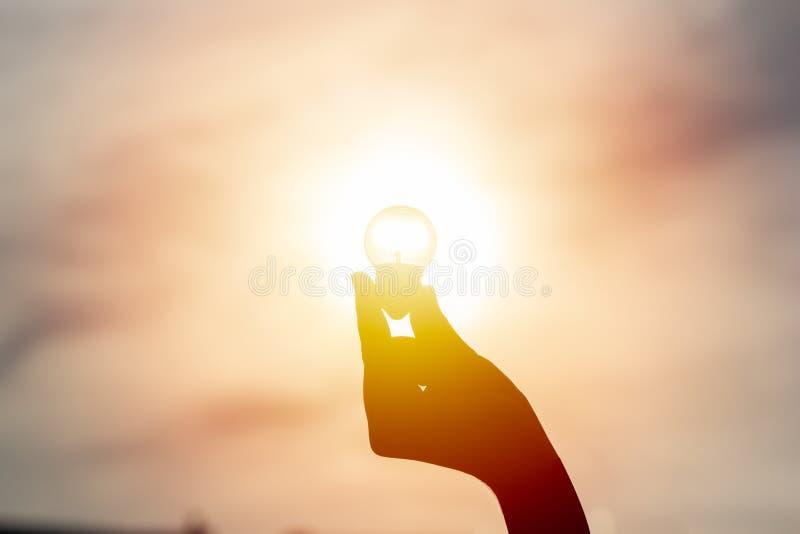 Idé och kreativitetbegrepp Konturhand som rymmer den ljusa kulan fotografering för bildbyråer