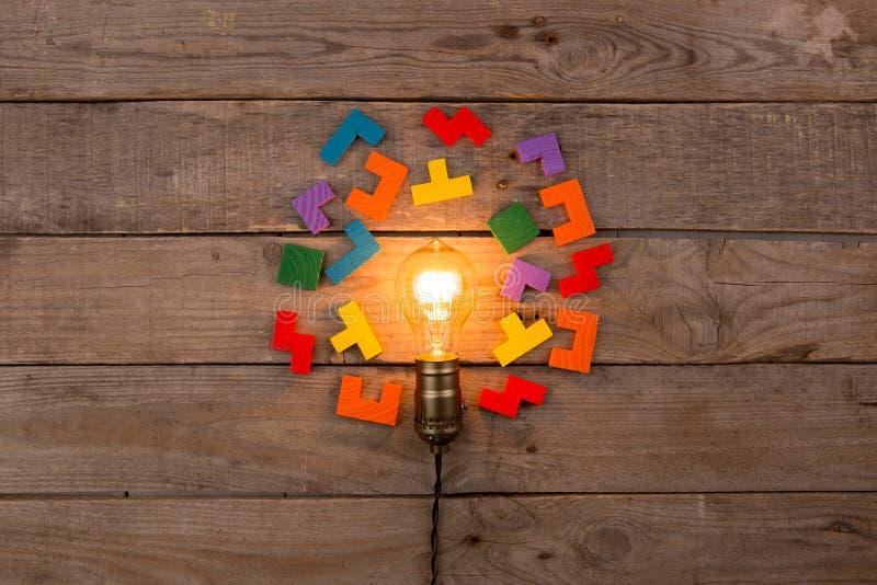 Idé och teamworkaffärsidé, glödande ljus kula för tappning och figursåg på träbakgrunden royaltyfria foton
