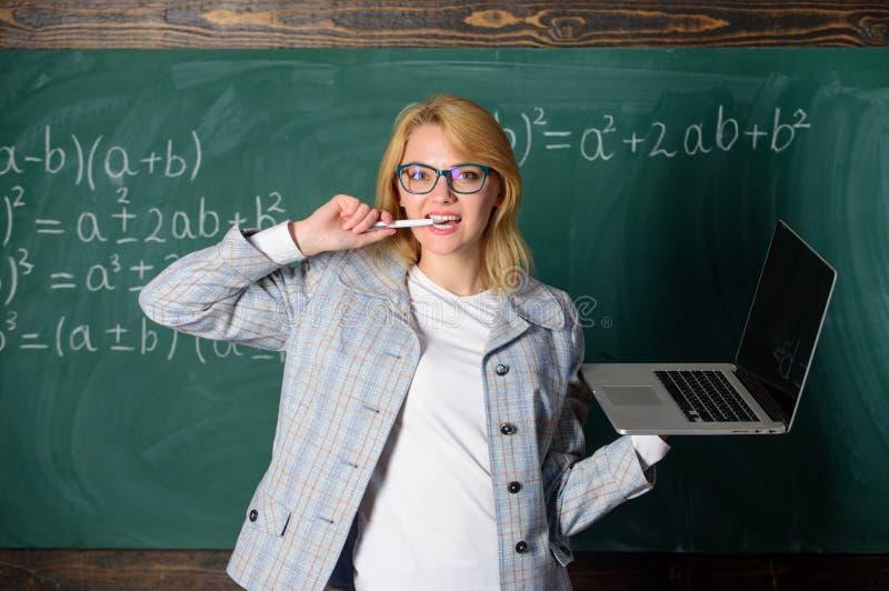 Idé på hennes mening Glasögon för kvinnalärarekläder rymmer bärbara datorn som surfar internet Smart klyftig dam för utbildare me arkivfoton