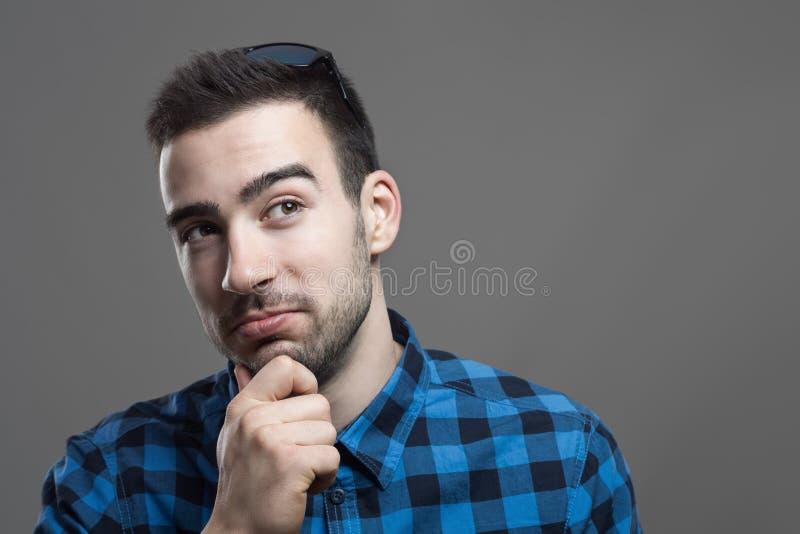 Idébegrepp av den unga lyckliga mannen med handen på hakan som ser upp på att tänka för copyspace royaltyfri foto