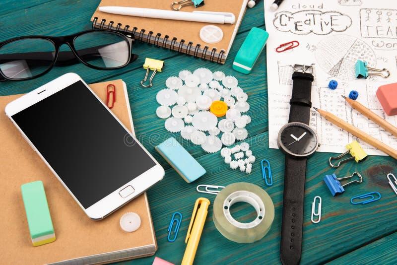 Idébegreppet - ringa, håll ögonen på, notepads, blyertspennor och kontorssupplien arkivbild