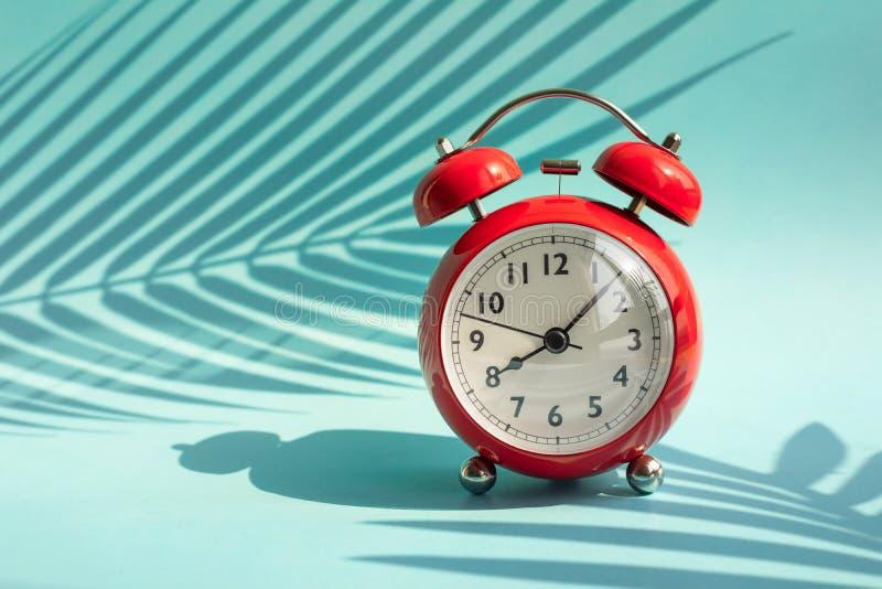 Idée de concepts d'heure d'été avec le réveil et l'ombre tropicale de feuille sur le fond coloré Décoration de vacances image stock