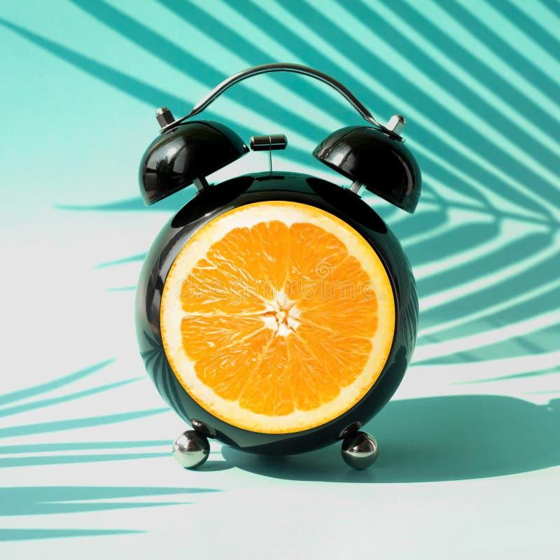 Idée de concepts d'heure d'été avec le réveil et l'ombre tropicale de feuille sur le fond coloré Décoration de vacances images stock