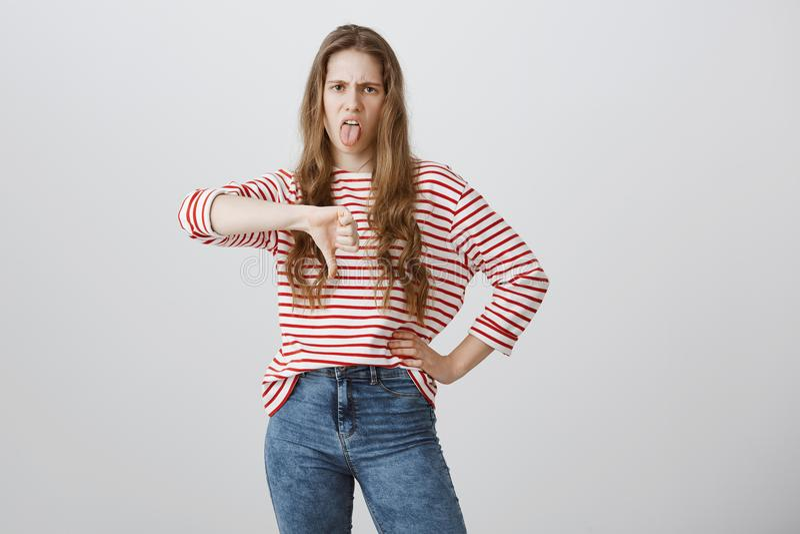 Idée terrible, aversion d'apparence de fille Jeune femme émotive contrariée fronçant les sourcils, collant la langue et montrant  photographie stock libre de droits