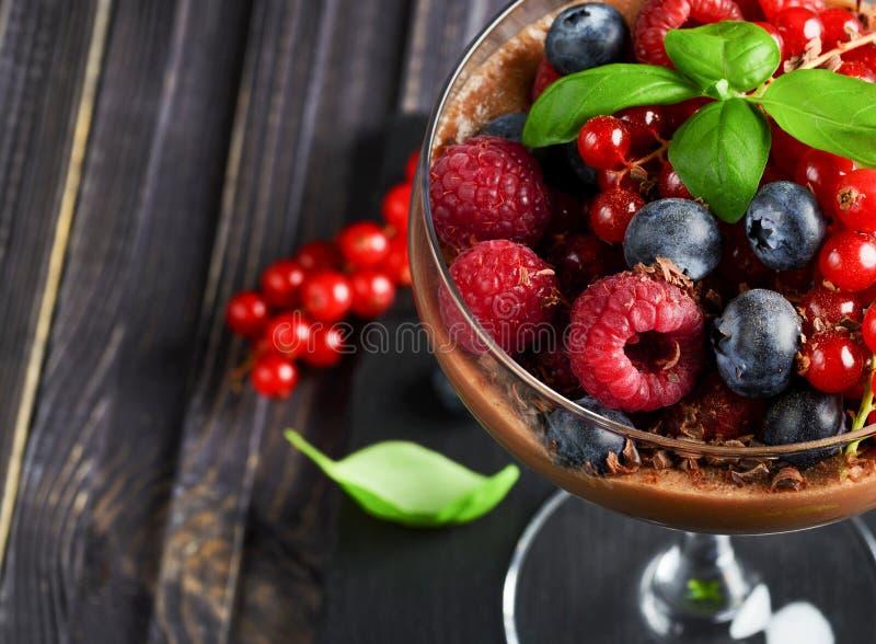 Idéer för ett sunt bantar Diet-parfait för chokladmousse med nya bär av hallon, blåbär och röda vinbär i a fotografering för bildbyråer