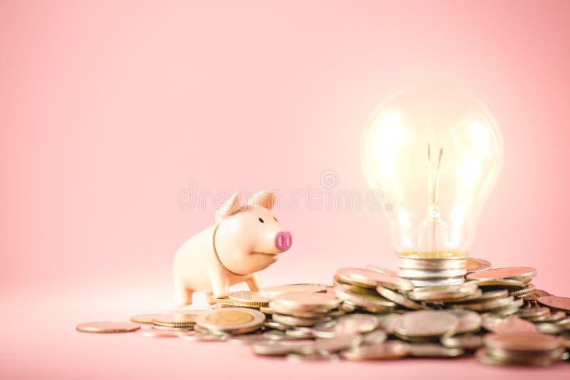 Idées créatives de sauver le concept d'argent avec l'ampoule et la tirelire sur la pile de pièces de monnaie Planification des af image stock