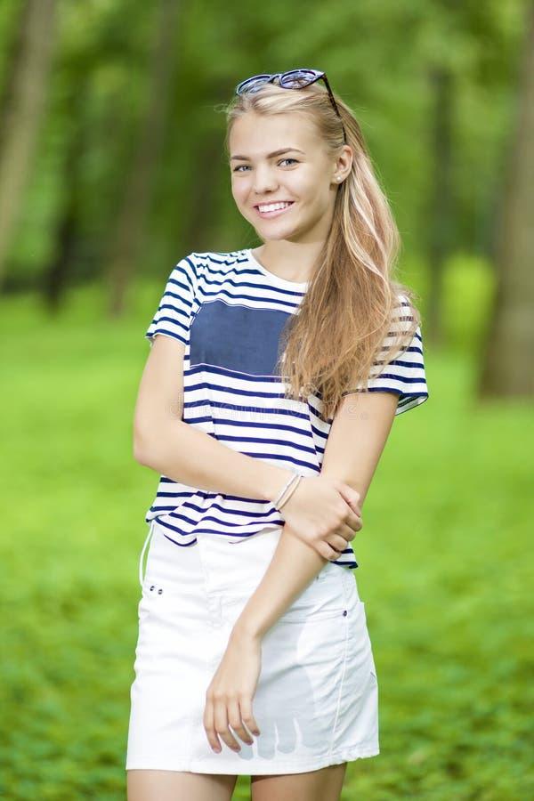 Idées de mode de vie d'adolescent Adolescente de sourire heureuse dans le T-shirt rayé posant dehors dans la forêt photos libres de droits