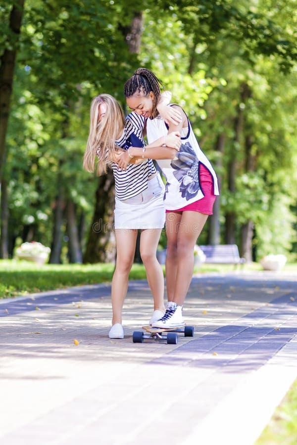 Idées de mode de vie d'adolescent Deux amies adolescentes ayant l'amusement Longboard de patinage dans le parc dehors photos libres de droits