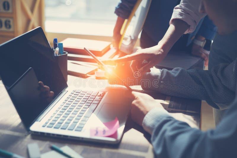 Idéia do negócio Equipe de Digitas que discute o plano de funcionamento novo Portátil e documento no escritório do espaço aberto fotos de stock royalty free