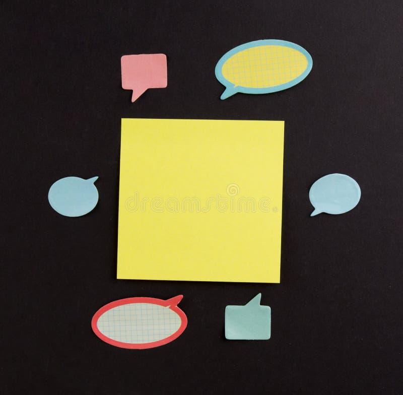 Idékläckning- och idébegrepp Stor gul klibbig anmärkning som omges av många små dialoganmärkningar på målbräda royaltyfria foton