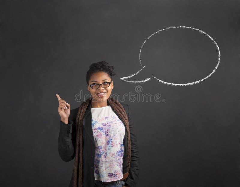 Idén och anförande för afrikansk kvinna bubblar den bra på svart tavlabakgrund royaltyfri bild
