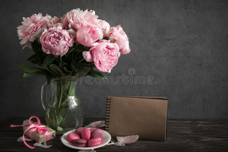 Idérik åtlöje upp med en härlig bukett av rosa pionblommor, gåvaasken, makron och tappninganteckningsboken royaltyfri bild