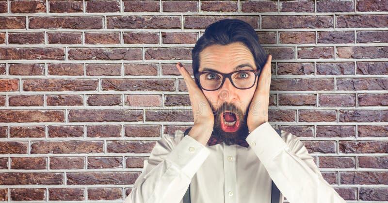 Idérik affärsman som ser förvånad, medan stå mot tegelstenväggen arkivfoton