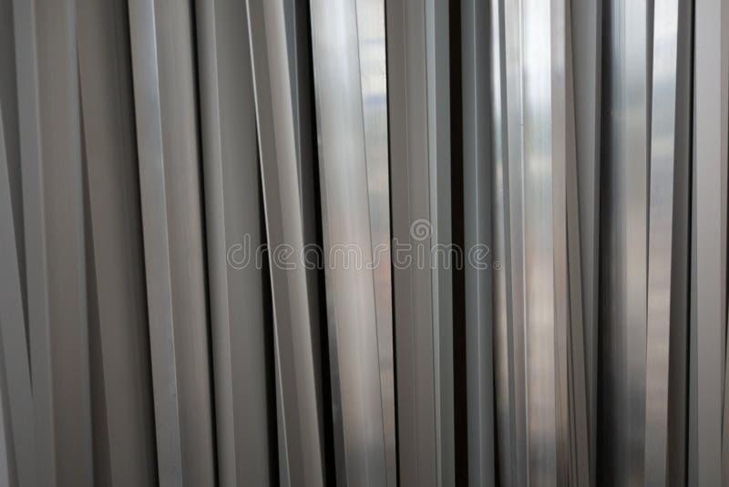 Idérik bakgrund från den aluminum profilen av det olika tvärsnittet royaltyfria bilder